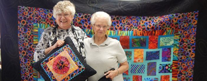Photo of 2 female quilters with quilt